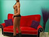Ebony TS chick wanks off on the red sofa