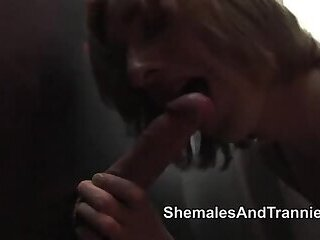 Two shemales suck cocks at the gloryhole